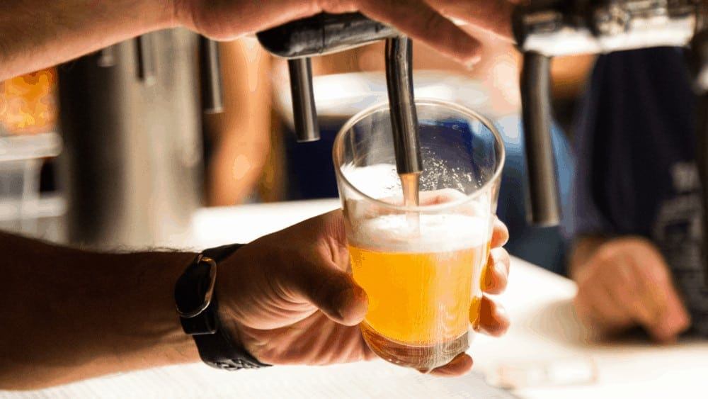 Person pouring beer from a tap