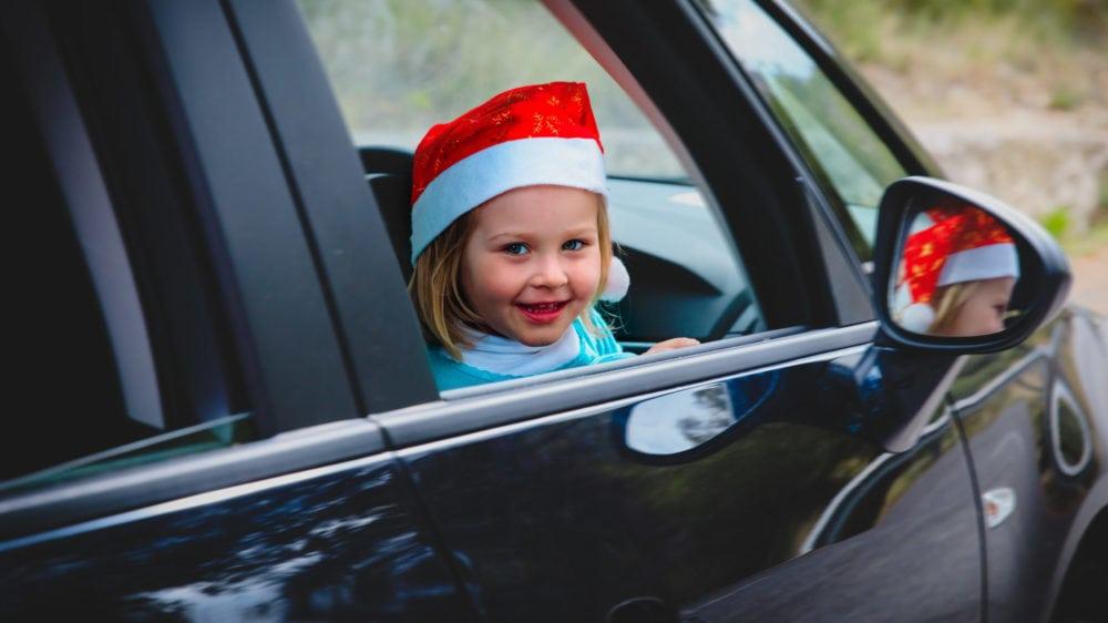 Girl wearing Santa hat in car